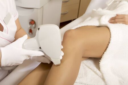 Young brunette woman receiving laser therapy removal on legs. Spa studio shot photo