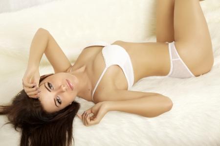 femme nue: Belle jeune femme blonde en lingerie couch�e sur le lit Banque d'images