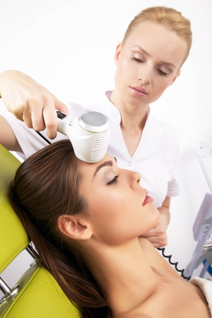 beauty treatment clinic: Portrait of attractive beautiful young adult brunette woman having a stimulating facial treatment from a therapist on the table in proffessional clinic spa Stock Photo