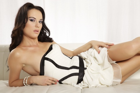Beautiful and attractive female brunette woman posing in white and black dress on the sofa photo