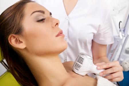 Portrait of attractive beautiful young adult brunette woman having a stimulating facial treatment from a therapist on the table in proffessional clinic spa photo
