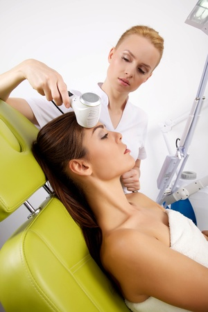stimulating: Portrait of attractive beautiful young adult brunette woman having a stimulating facial treatment from a therapist on the table in proffessional clinic spa Stock Photo