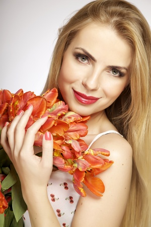Beautiful and attractive smiling blonde young adult girl with the bouquet of red and yellow tulips flowers isolated on a white background photo