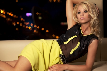 black dress: attractive blond woman in black dress sitting on the couch
