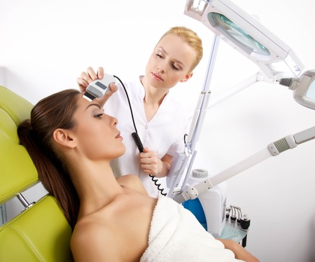beauty salon face: Portrait of attractive beautiful young adult brunette woman having a stimulating facial treatment from a therapist on the table in proffessional clinic spa Stock Photo