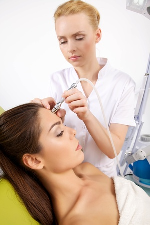 dermatologo: Ritratto di giovane attraente bella donna adulta bruna con una stimolante trattamento viso da un terapeuta sul tavolo in spa clinica rimanendo professionale