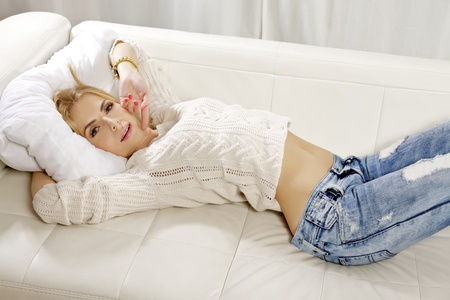 Beautiful and attractive young adult smile blonde woman posing in blue jeans and grey sweater on the white sofa photo