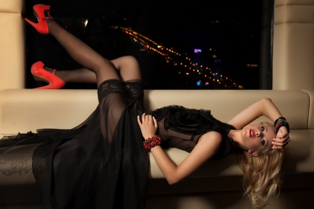 woman on couch: attractive blond woman in black dress sitting on the couch