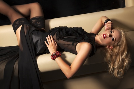 attractive femme blonde en robe noire assise sur le canap? photo