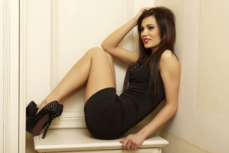 Beautiful and attractive young adult female brunette sensuality woman posing in black dress in apartment photo