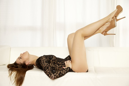 Beautiful and sexy young adult brunette woman wearing black lingerie in sofa Stock Photo