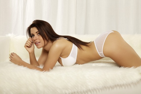 Beautiful and sexy young adult brunette woman wearing white lingerie on the sofa photo