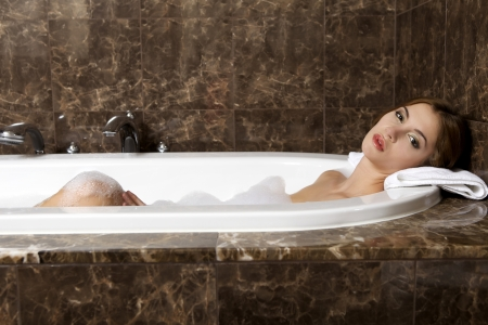 Attractive brunette woman in bath relaxing. Closeup of young woman in bathtub bathing Stock Photo - 21381765