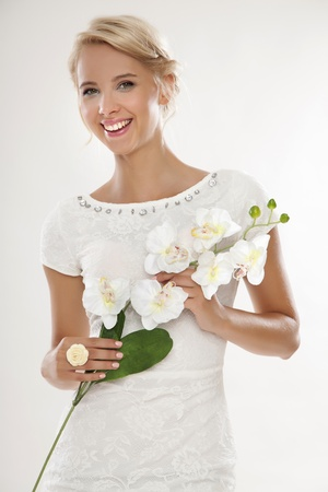 beautiful bride: Portrait of blonde young bride in white wedding dress happy smiling with flowers in hands isolated on white background Stock Photo