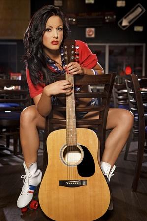 Joven adulto americano mujer morena estilo con la guitarra