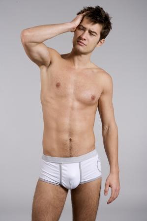 nude boy: Portr�t der jungen erwachsenen Mann schl�frig nackten muskul�sen Oberk�rper in wei�en H�schen auf grauem Hintergrund isoliert