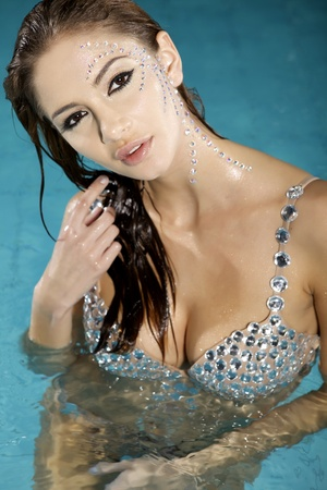 beautiful brunette woman with damond make up in swimmingpool photo
