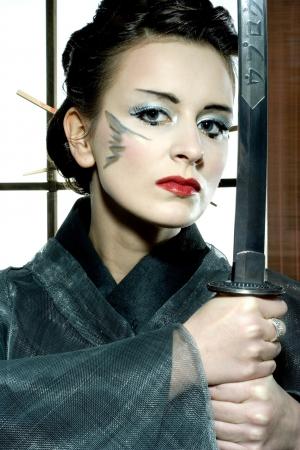beautiful japanese grey kimono woman with samurai sword in traditional room photo