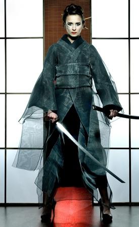 mooie Japanse grijze kimono vrouw met samurai zwaard in traditionele kamer