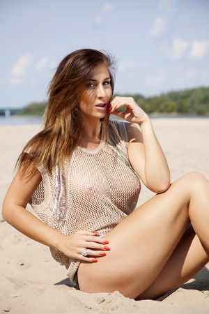 Young adult attractive beautiful brunette woman in brown transparent sweater on the beach photo