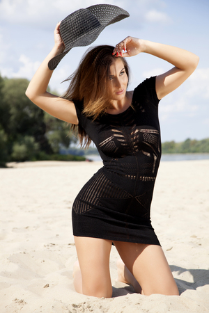Young adult beautiful brunette woman in black dress and black hat on the beach photo