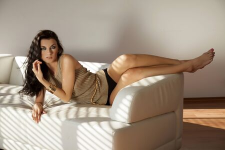 Beautiful and attractive female brunette woman posing in golden brown sweater on the white sofa couch in shadow photo