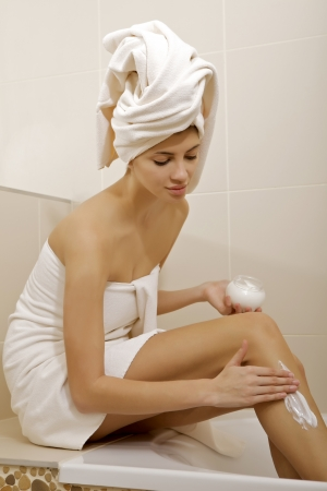 Attractive young adult woman applying moisturizer cream on the legs in bathroom photo
