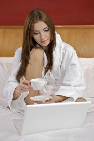 Portrait of beautiful brunette woman with laptop on bed at bedroom Stock Photo - 23528214
