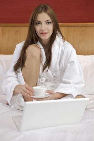 Portrait of beautiful brunette woman with laptop on bed at bedroom Stock Photo - 23528215