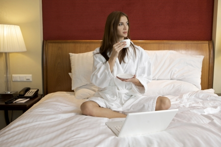 Portrait of beautiful brunette woman with laptop on bed at bedroom Stock Photo - 23528216
