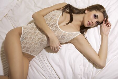 Beautiful young blonde woman in lingerie lying on the bed photo