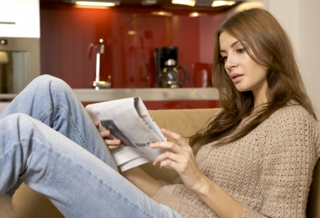 mid adult beautiful woman drinking coffee and reading news photo