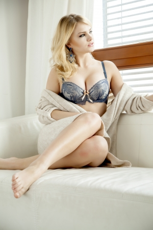 Beautiful and sexy young adult sensuality blonde woman in blue lingerie and brown sweater on the white sofa in window on luxury apartment photo