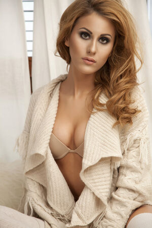 Young slim sexy and attractive blonde woman in brown sweater against the window photo