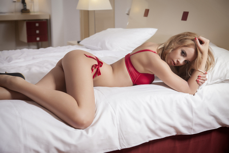 Young sexy blond woman in sexy red lingerie lying on the bed photo