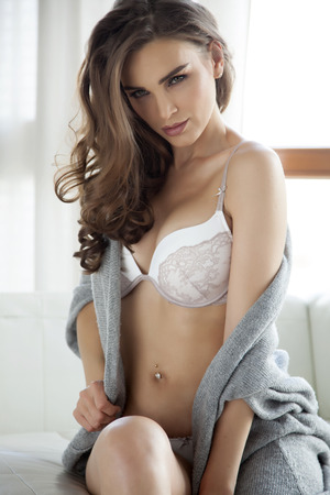 Beautiful and sexy young adult sensuality brunette woman in white lingerie and grey sweater on the white sofa in window on luxury apartment photo