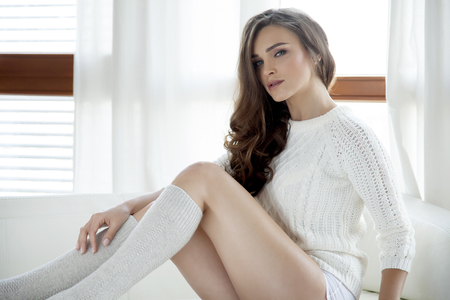Beautiful and sexy young adult sensuality brunette woman in white sweater and grey socks on the white sofa in window on luxury apartment photo