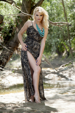 Fashion portrait of young sensual blonde woman in garden. Beauty summertime