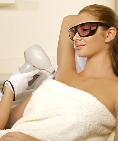 Young brunette woman receiving laser therapy. Spa studio shot Stock Photo - 30542820