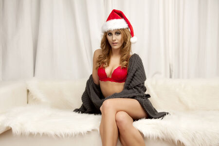 Beautiful young adult brunette woman as santa girl in red lingerie - christmas portrait photo