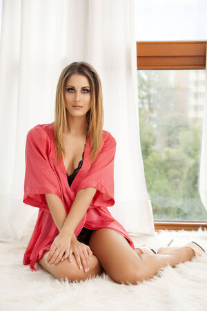 Beautiful and sexy young adult sensuality brunette woman in black lingerie and red bathrobe on the window on luxury apartment photo