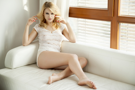 Beautiful and sexy young adult sensuality blonde woman in white lingerie on the white sofa in luxury apartment