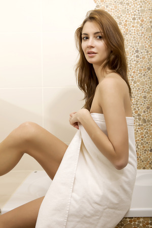 Portrait of beautiful young adult sensuality sexy and attractive pretty brunette woman in home bathroom with white towel on her body photo