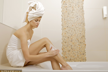 Attractive young adult woman applying moisturizer cream on the legs in badroom photo