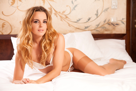 Beautiful and sexy young adult attractive sensuality pretty blonde babe woman in white lingerie on the bed in bedroom on luxury style exclisive hotel apartment Reklamní fotografie