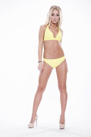 sexy young girls: Сексуальная блондинка женщина, носить желтую купальный костюм, изолированных на белом фоне. Идеальное тело