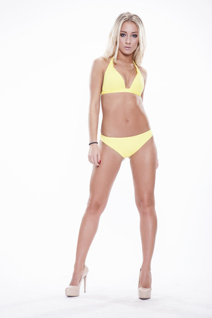niñas en bikini: Mujer rubia atractiva vistiendo trajes de baño de color amarillo sobre fondo blanco. Cuerpo perfecto
