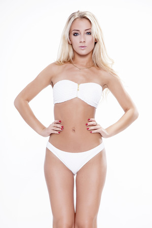 perfect female body: Sexy blonde woman wearing white swimwear isolated on white background. Perfect body