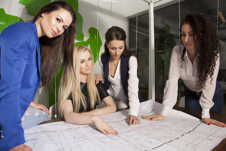 corporate women: Four beauty young adult businesswomen at office working with laptop