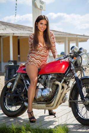 Muchacha del motorista en retro de la motocicleta - Retrato de una mujer fresca en una moto de la vendimia Foto de archivo